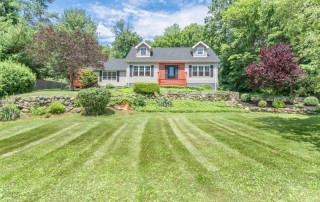 front of the home with a manicured lawn
