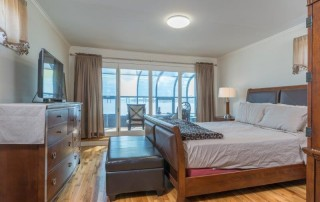 bedroom with wood floors and views of the water
